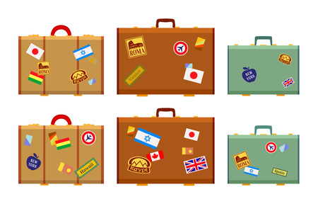 Travelers suitcases with the stickers. The objects are isolated against the white background and shown from one side