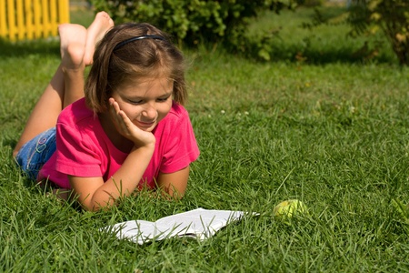 Girl reading a book lying on the grass
