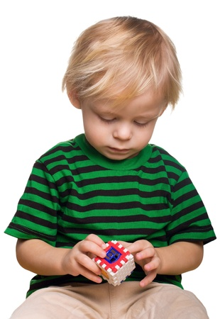Serious boy assemble house from  puzzles