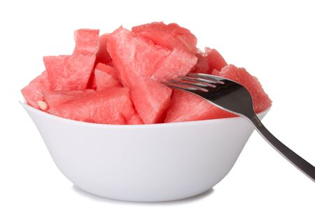 watermelon pieces in bowl with fork isolated on white photo