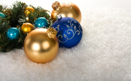 gold and blue christmas balls with branch fir tree on snow