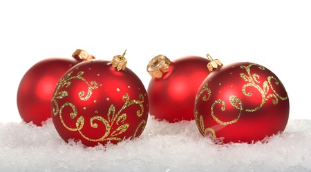 red christmas balls with pattern on snow on white background