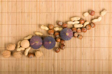 Background figs, peanuts, hazelnuts, walnuts on bamboo mat Stock Photo