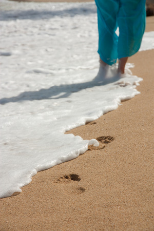 Woman walking on sand beach leaving footprints Stock Photo