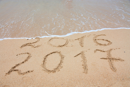 New Year 2017 is coming concept - inscription 2017 and 2016 on a beach sand, the wave is covering digits 2016