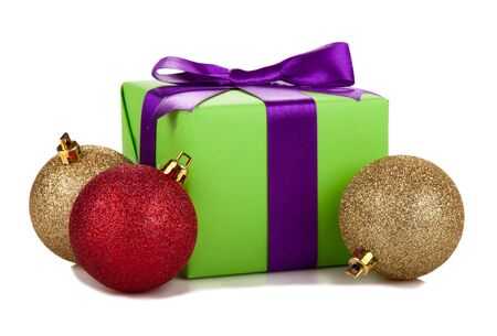 green gift box with purple ribbon and balls