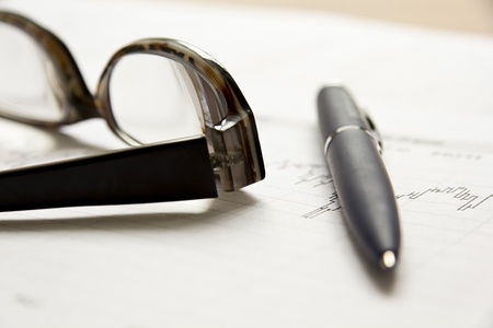 Stock chart with glasses and a pen on the table