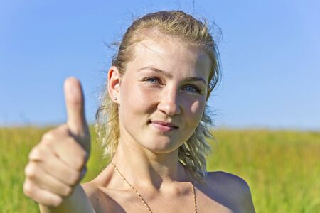 young beautiful woman showing thumb up and smiles