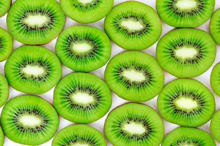 kiwi, cut into slices laid on a white background