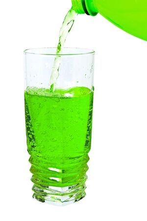 cold green soda in a tall glass, pour from the bottle photo