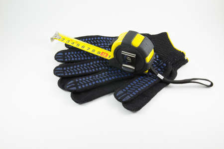 white work: Measuring tape and work gloves on a white background