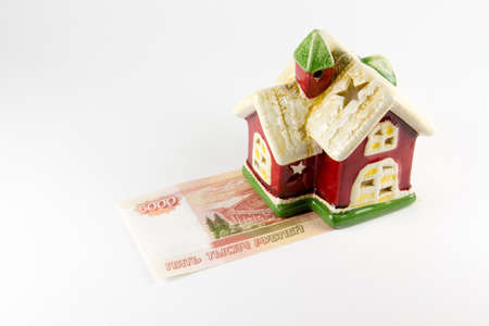 House and five thousand rubles money on a white background