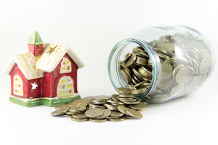 House and a glass jar with coins on a white background