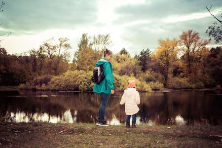Mom and daughter on the shore of a forest lake in autumn