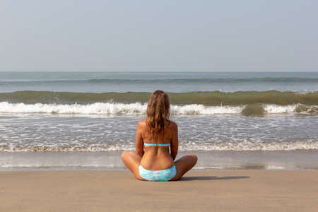 Young woman meditates sitting on the ocean