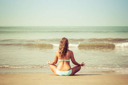 Young woman meditates sitting on the ocean Stock fotó