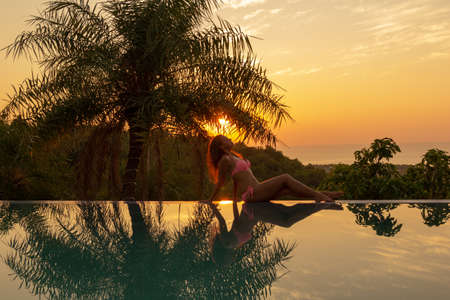 Portrait of a young woman on the edge of the pool at sunset