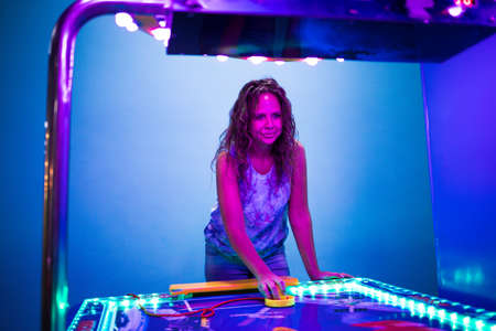 Young woman plays air hockey in an entertainment center