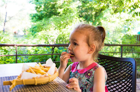 child eats french fries. not healthy food Stock Photo