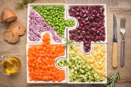 Delicious fresh pieces of vegetables of carrots, cucumber, potatoes, beets and peas close-up with fresh onion and olive oil on a bag cloth on a rustic gray table.