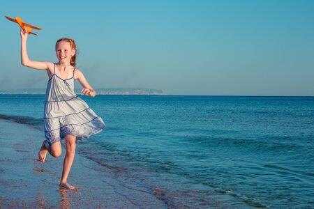 A happy red-haired child playing with an orange toy plane and running happily along the sandy beach of the sea against a clear blue sky and enjoying the rays of the summer sun and freedom.