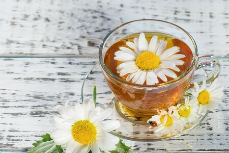 A cup of tea standing on a wooden, white table, in the flowers of the daisy field, to which the ladybug flew.