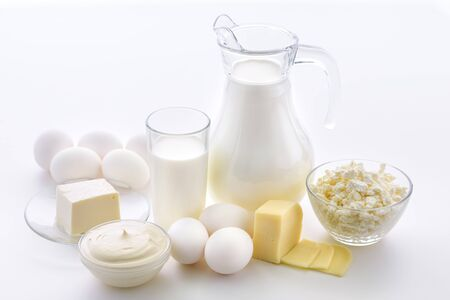Milk composition with a jug and a glass of milk with cheese and eggs next to a plate of cottage cheese and sour cream on a white background. Zdjęcie Seryjne