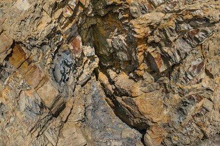 Texture of a dark yellow granite stone or background for design.Surface of the rock with an abstract pattern.
