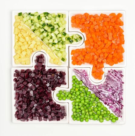Raw vegetables carrots, peas, onions, cucumber, potatoes, beets cut into cubes lie on puzzles in the form of puzzles and gather in a single large dish.