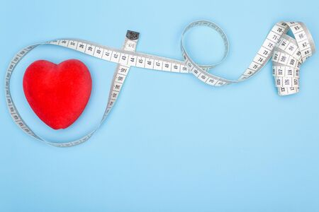 Heart, flexible ruler on a blue background as a concept for losing weight and healthy lifestyle.Copy space for text.Conceptual background with pharmaceutical themes on a blue background.