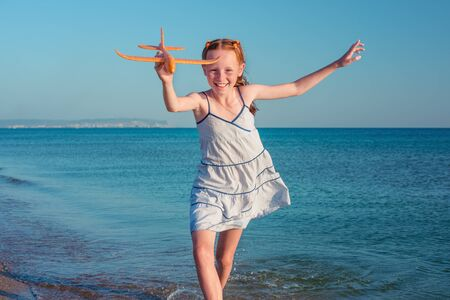 Happy little girl is playing with a plane at sea. In the background a beautiful blue sea.