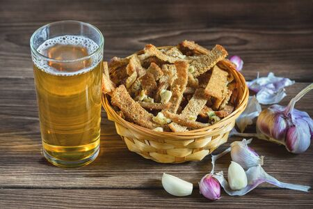 Home snack for beer as rye crisps with garlic, lying in a wooden table in the rays of sunlight, next to it there is a glass with freshly poured beer.