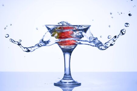 Frozen explosion of freshness from water, in a cocktail glass with strawberries, on a white background.