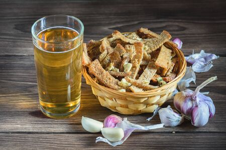 A bouquet of fresh beer and snacks with homemade, salted, rye rusks with garlic for beer, lie on a wooden table, in the rays of sunlight.