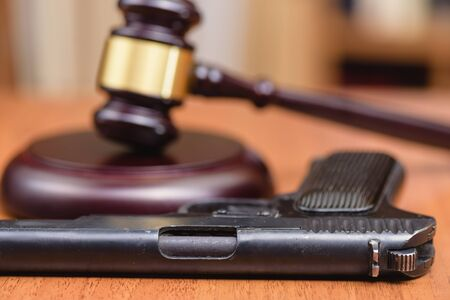 Judge hammer, pistol on the background of wooden table. Concept is not legally carrying weapons. Crime with weapon.