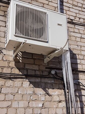 On a white brick wall, a white air conditioner hangs from which large, ice icicles hang.
