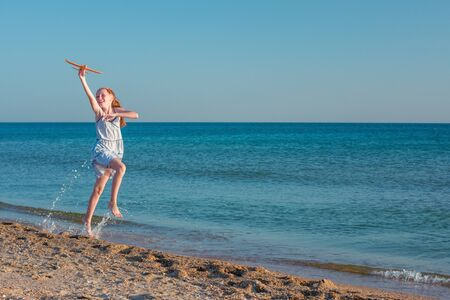 A beautiful red-haired girl, playing with a toy airplane, jumps over the waves of the sandy shore of the sea against the background of a clear blue summer sky and rejoices in the rays of the sun and freedom.