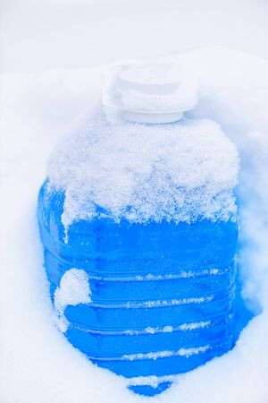 Non-freezing liquid for washing car glass in winter. Winter car wash glass liquid in the snow. Car non-freezing fluid in frost on snow. Blue liquid in frost during day.