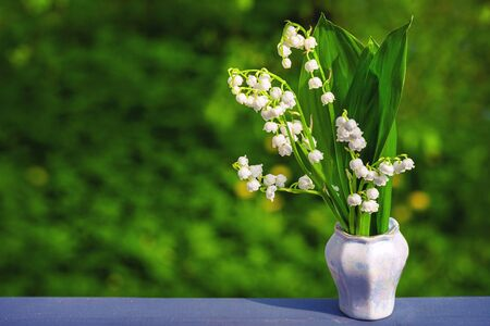 Bouquet of spring flowers standing in a vase on a wooden table with copy space.Lily of the valley. Flower Spring Sun White Green Background Horizontal. Ecological background Blooming lily of the valley on green grass background in the sunlight. Spring flower lily of the valley.