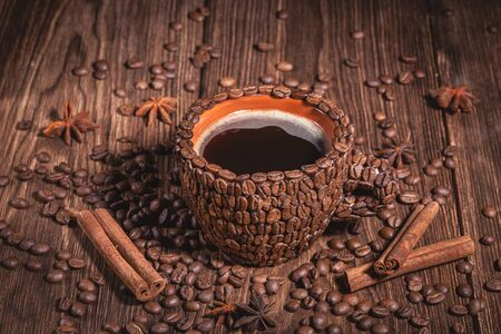 Background for coffee restaurant with cup of coffee made from roasted arabica beans. Coffee Cup Table Tree Coffee Grain Top View Cinnamon Stick Star Anise Close-up.  Фото со стока