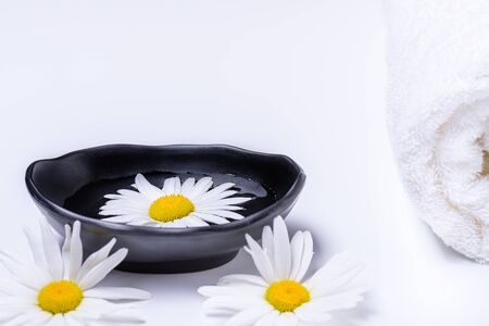 Natural oils for SPA. Spa treatment concept with terry towel and black plate with liquid in which white daisy floats. White terry towel and white daisies lying white background.Flat lay composition. Copy space for text.  스톡 콘텐츠