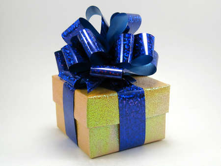 Gift in a yellow box with a  blue bow on a white background photo