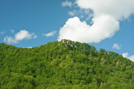 Summer landscape with a trees, mountains, clouds and blue sky photo
