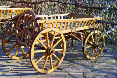 cartage: Old wooden cartage cart near fence
