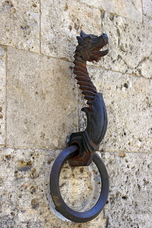 hitching post: Old horse hitching ring on a historical wall with dragon head