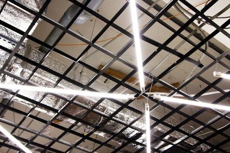 Las lámparas fluorescentes cuelgan en el techo de un edificio industrial: en una fábrica, en una fábrica Foto de archivo