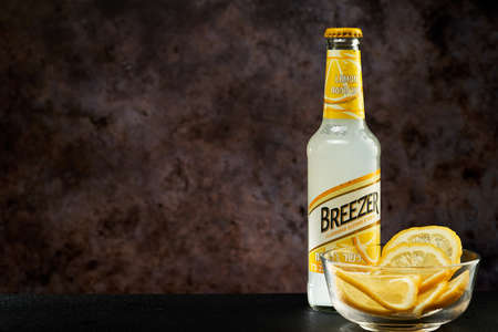 Tel-Aviv,Israel - 20.04.21.Bacardi breezer light alcohol beverage in lemon taste with the fresh lemon cuts inside the glass plate.