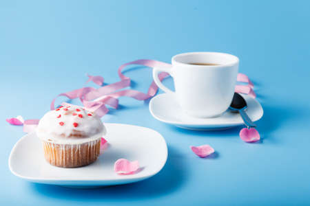 racy: Colorful muffin on saucer with flower petal and ribbon