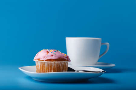 colorific: Colorful muffin on saucer. Blue background
