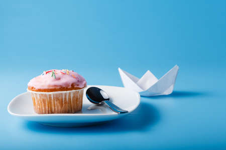 colorific: Colorful muffin on saucer with paper boat. Blue background